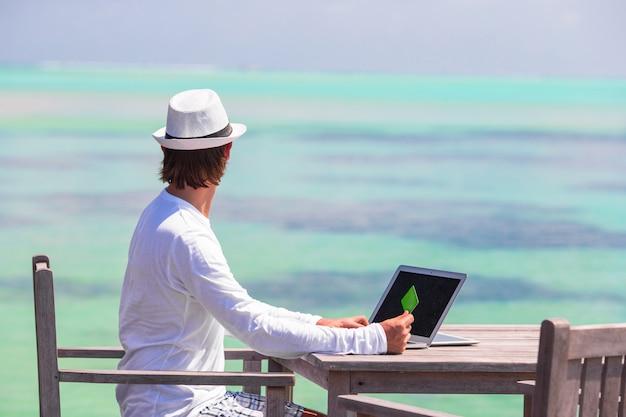 Junger mann, der an laptop mit kreditkarte am tropischen strand arbeitet