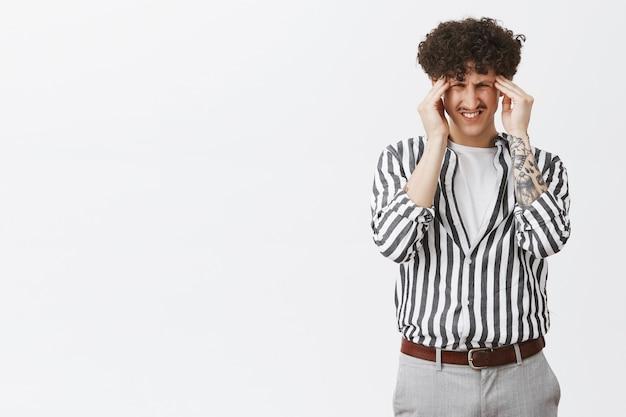 Junger mann, der an migräne leidet, sich schwindelig oder kopfschmerzen fühlt