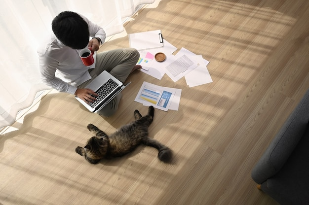 Junger mann, der an seinem laptop mit seiner katze in bequemem zuhause arbeitet.