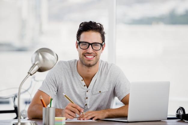 Junger mann, der an seinem schreibtisch arbeitet