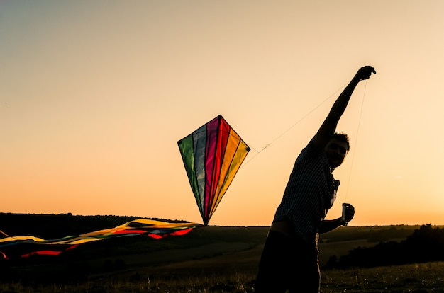 Junger mann, der anfängt, einen bunten drachen im sonnenunterganghimmel zu fliegen