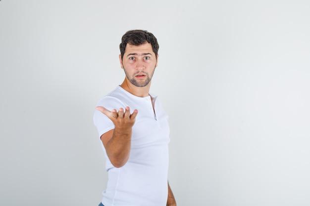 Junger mann, der arm in fragender geste im weißen t-shirt hebt und wütend schaut