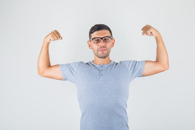 Junger mann, der arme hebt und bizeps im grauen t-shirt, brillenvoransicht zeigt.