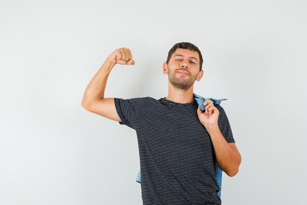Junger mann, der armmuskeln zeigt, die jacke im t-shirt halten und zuversichtlich schauen