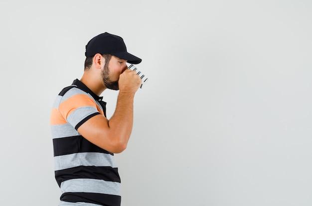 Junger mann, der aromatischen kaffee im t-shirt, in der mütze und im nachdenklichen schauen trinkt.