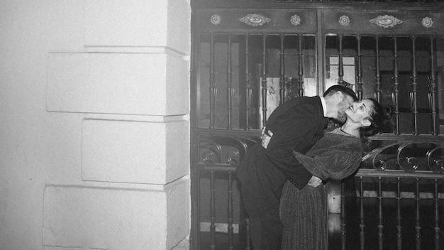 Junger mann, der attraktive frau auf straße küsst und verbiegt