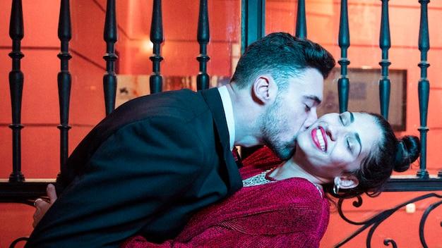 Junger mann, der attraktive nette frau nahe toren küsst und verbiegt