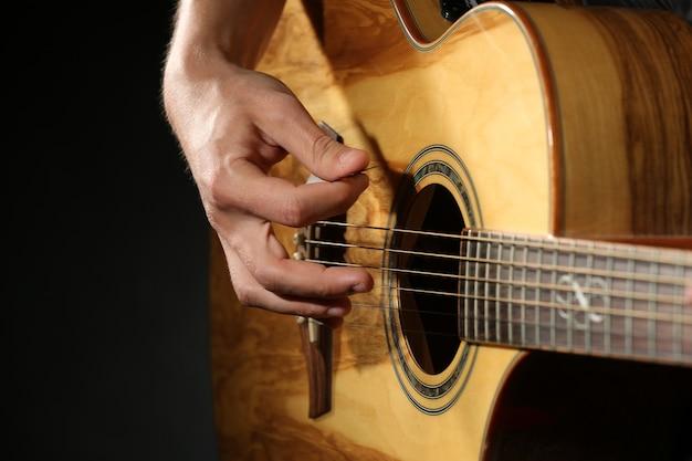 Junger mann, der auf akustischer gitarre spielt