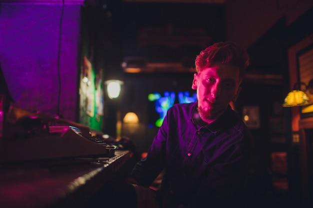 Junger mann, der auf alte schreibmaschine schreibt. in dunkler beleuchtung, restaurant, moderne kleidung, alte schriftstellergewohnheiten