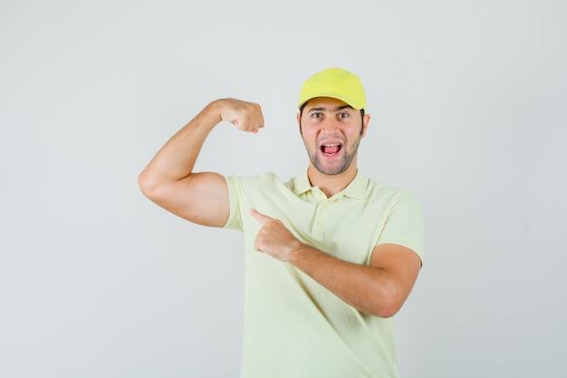 Junger mann, der auf armmuskeln in gelber uniform zeigt und mächtig aussieht