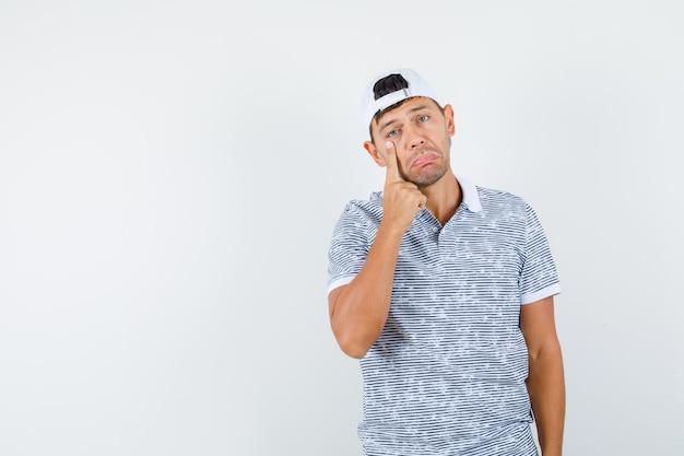 Junger mann, der auf auge in t-shirt und mütze zeigt und müde aussieht