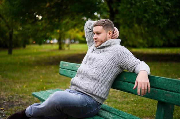 Junger mann, der auf bank im park sich entspannt