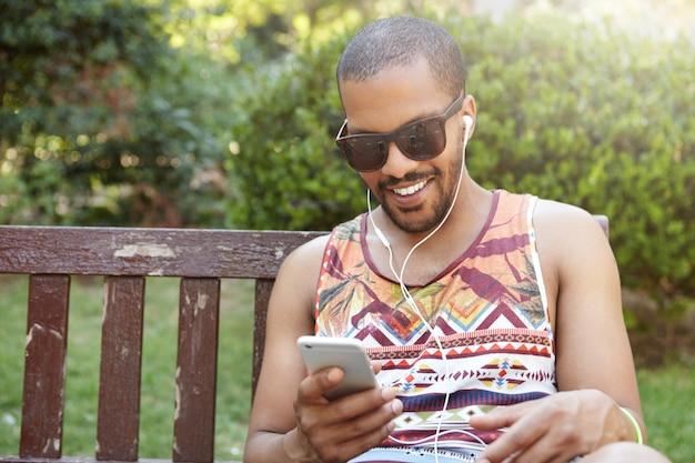 Junger mann, der auf bank im park sitzt und musik hört