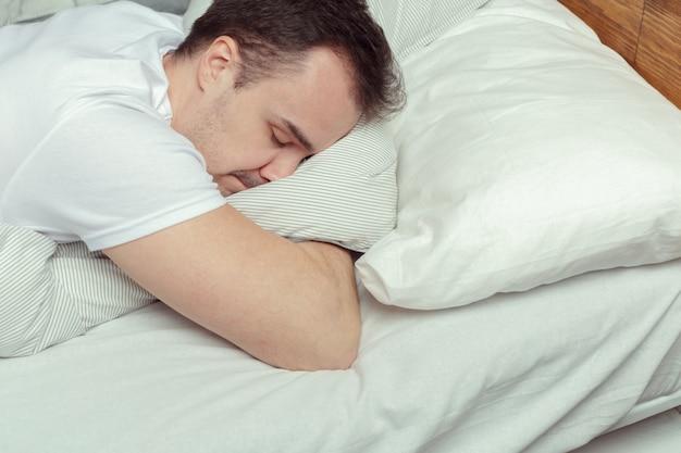 Junger mann, der auf bett im schlafzimmer schläft