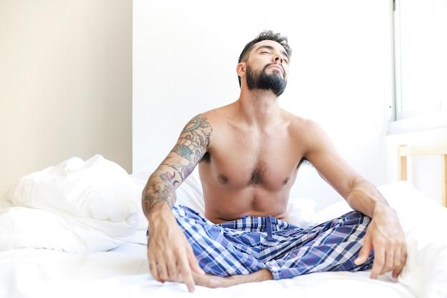 Junger mann, der auf bett im schlafzimmer sitzt