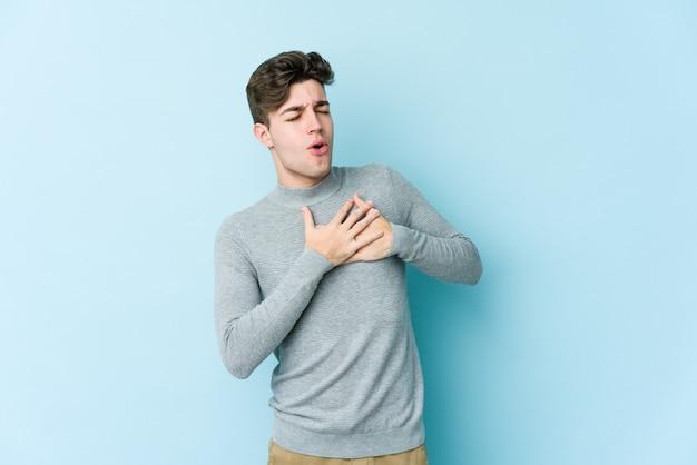 Junger mann, der auf blauer wand isoliert ist, hat freundlichen ausdruck und drückt handfläche zur brust