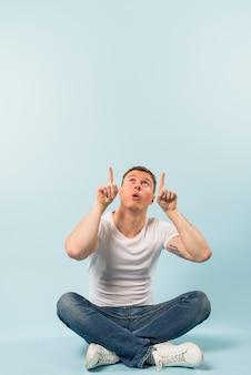 Junger mann, der auf boden mit den gekreuzten beinen sitzt, seine finger aufwärts gegen blauen hintergrund zeigend