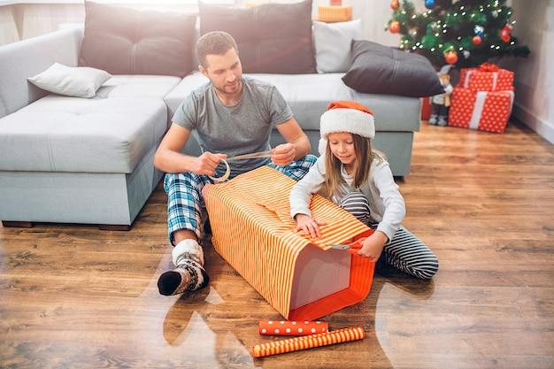 Junger mann, der auf boden mit kleinem mädchen sitzt und großen kasten geschenk verpackt.
