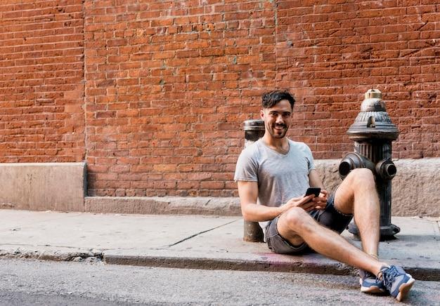 Junger mann, der auf bürgersteig unter verwendung des mobiles sitzt