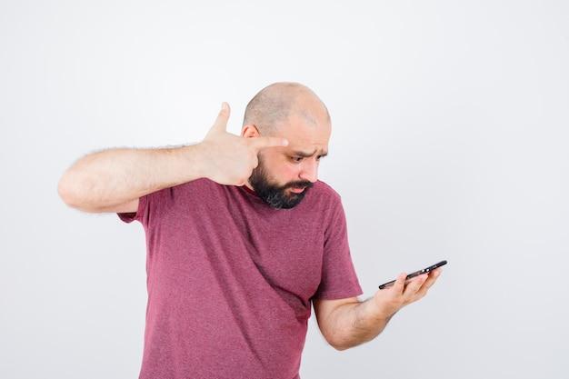 Junger mann, der auf das telefon schaut und eine waffengeste in rosa t-shirt zeigt und düster aussieht. vorderansicht.