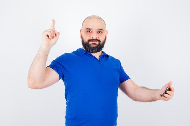 Junger mann, der auf das telefon schaut, während er in der vorderansicht des blauen hemdes nach oben zeigt.