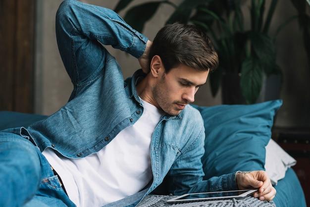 Junger mann, der auf dem bett betrachtet digitale tablette liegt