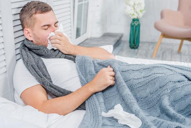 Junger mann, der auf dem bett mit dem gewebe liegt, das grippe oder allergie hat
