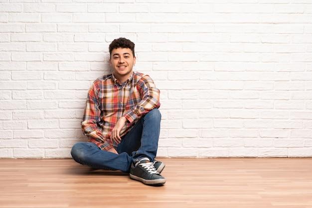 Junger mann, der auf dem boden hält die arme gekreuzt in frontaler position sitzt