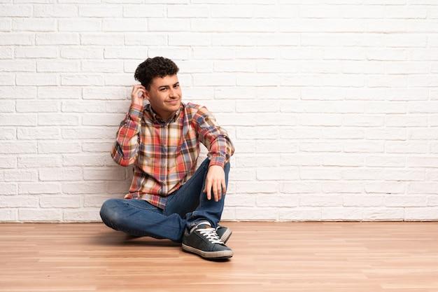 Junger mann, der auf dem boden hat zweifel sitzt