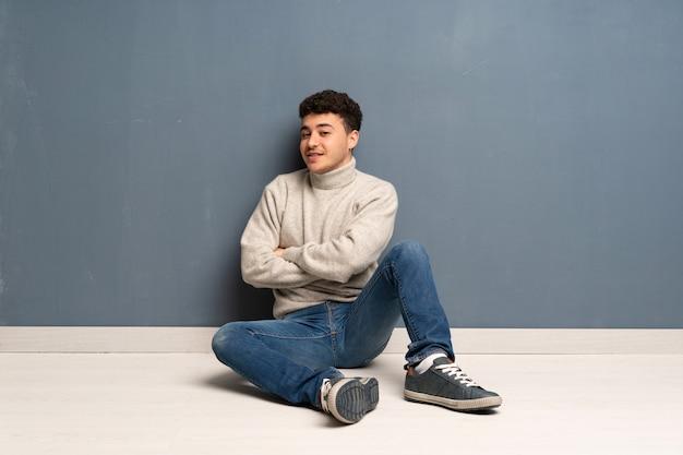 Junger mann, der auf dem boden mit den armen gekreuzt sitzt und vorwärts schaut