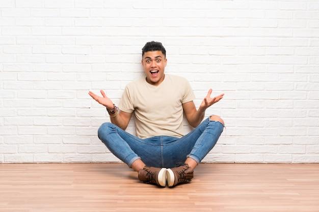 Junger mann, der auf dem boden mit überraschungsgesichtsausdruck sitzt