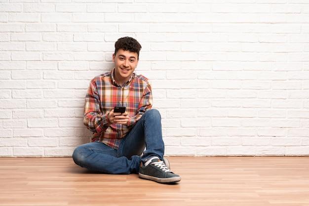 Junger mann, der auf dem boden sendet eine mitteilung mit dem mobile sitzt