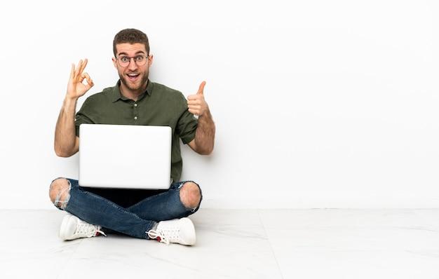 Junger mann, der auf dem boden sitzt und ein ok-zeichen und eine daumen-hoch-geste zeigt