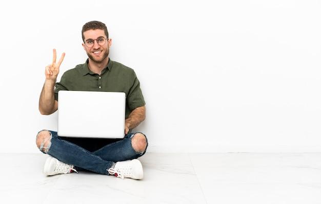 Junger mann, der auf dem boden sitzt und lächelt und victory-zeichen zeigt