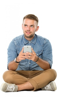 Junger mann, der auf dem boden sitzt und sich vorstellt, während er smartphone hält