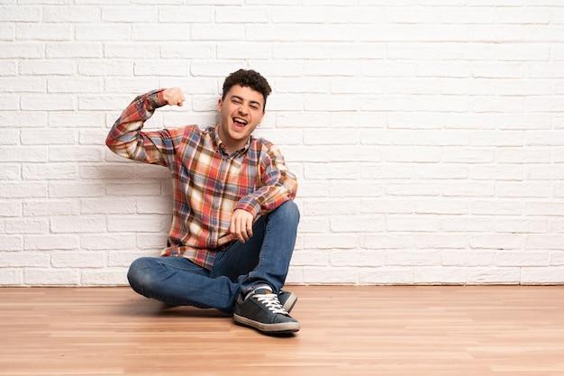 Junger mann, der auf dem boden tut starke geste sitzt