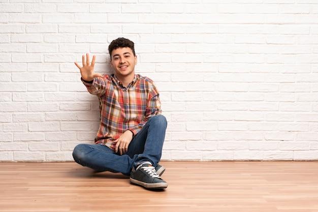 Junger mann, der auf dem boden zählt fünf mit den fingern sitzt