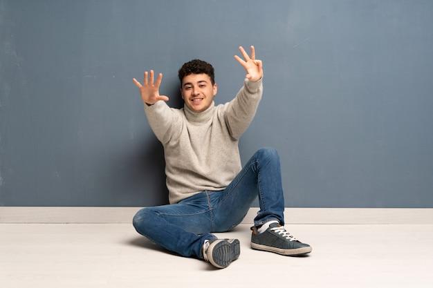 Junger mann, der auf dem boden zählt neun mit den fingern sitzt