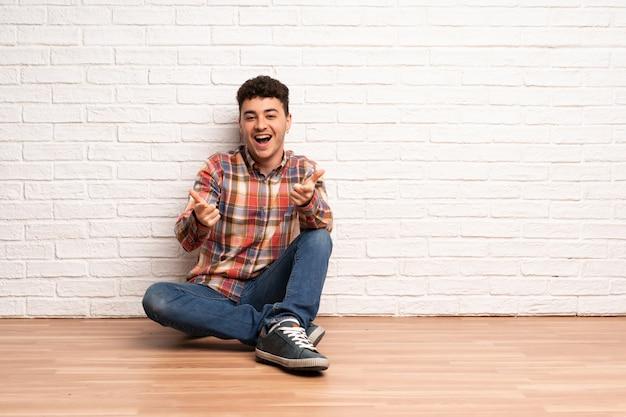 Junger mann, der auf dem boden zeigt auf die front und das lächeln sitzt