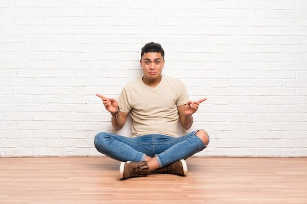 Junger mann, der auf dem boden zeigt auf die seitenteile hat zweifel sitzt