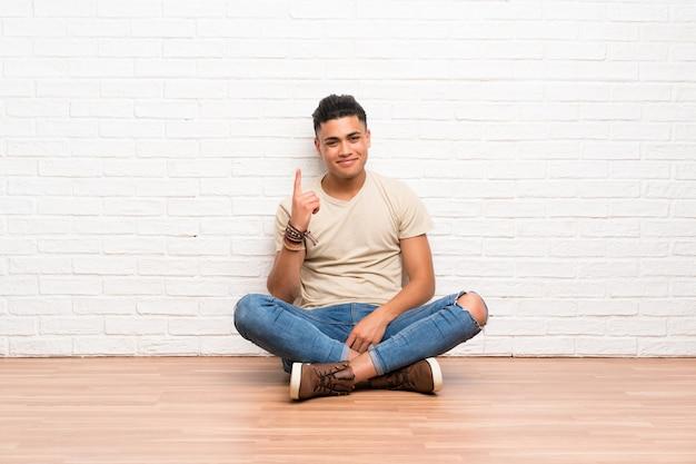 Junger mann, der auf dem boden zeigt mit dem zeigefinger eine großartige idee sitzt