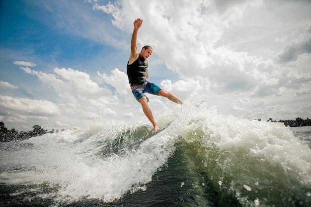 Junger mann, der auf dem brett hinunter den fluss gegen den himmel wakesurfing ist