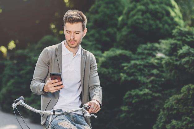 Junger mann, der auf dem fahrrad betrachtet smartphone sitzt
