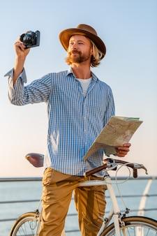 Junger mann, der auf dem fahrrad durch see in den sommerferien durch das meer auf sonnenuntergang reist und karte sightseeing hält, das foto vor der kamera macht