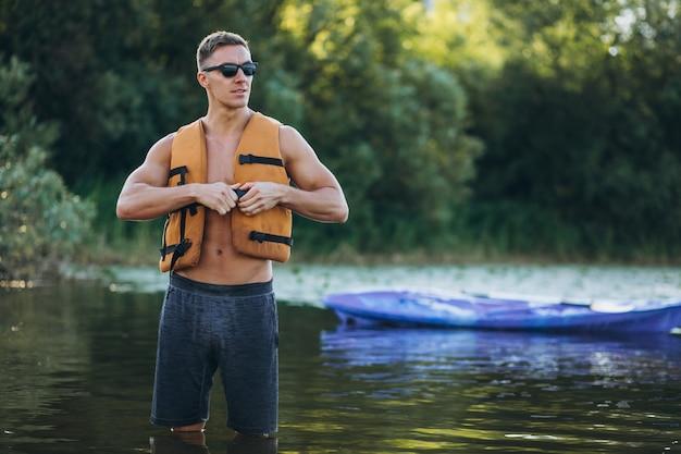Junger mann, der auf dem fluss kayak fährt