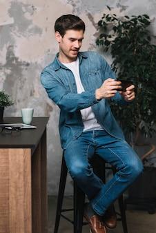 Junger mann, der auf dem schemel nimmt selfie durch mobiltelefon sitzt