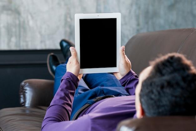 Junger mann, der auf dem sofa betrachtet digitale tablette mit schwarzer bildschirmanzeige liegt