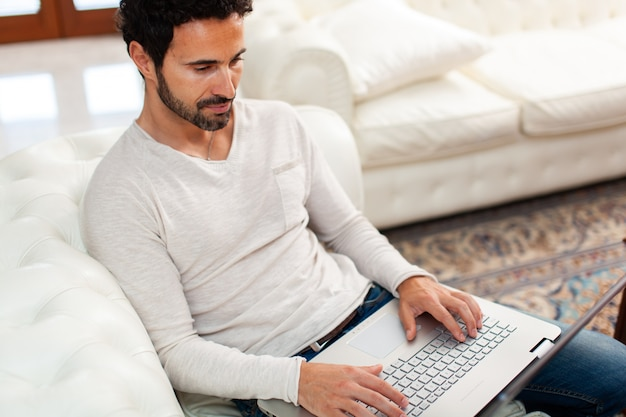 Junger mann, der auf dem sofa mit einem laptop entspannt