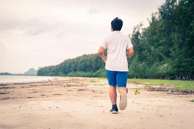 Junger mann, der auf dem strand rüttelt