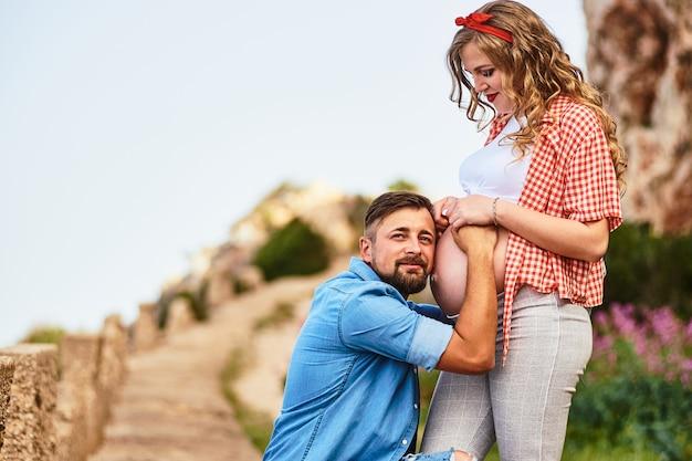 Junger mann, der auf den bauch seiner schwangeren frau hört